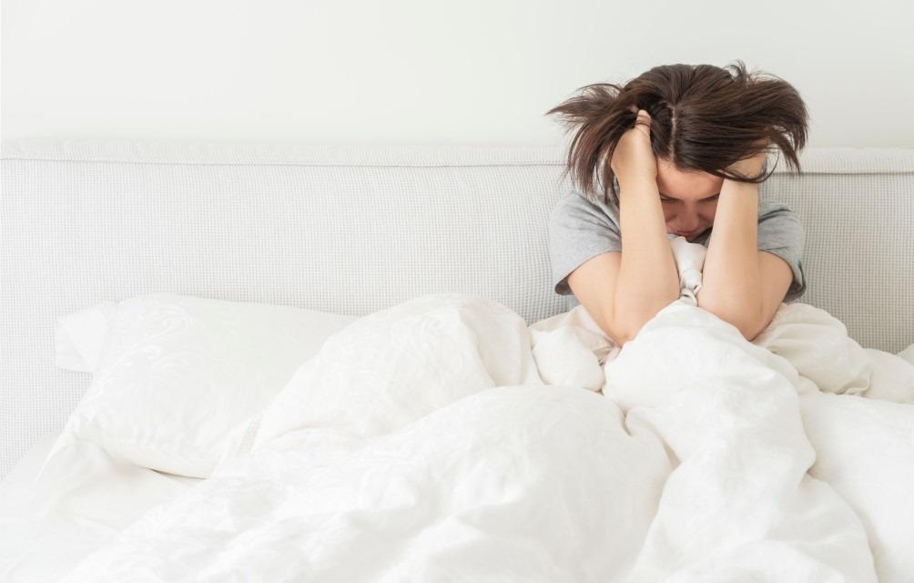 Frau verzweifelt in Bett